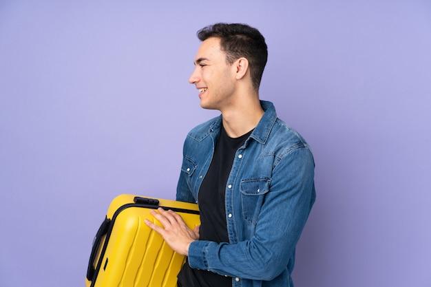 Jonge knappe man geïsoleerd op paarse muur in vakantie met reizen koffer