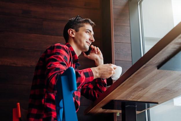 Jonge knappe man geniet van koffie in het café voor het raam