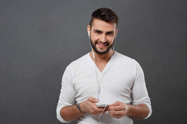 Jonge knappe man glimlachend bedrijf telefoon over grijze muur