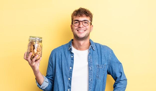 Jonge knappe man glimlachend gelukkig met een hand op de heup en zelfverzekerd. koekjes fles concept