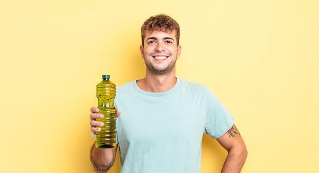Jonge knappe man glimlachend gelukkig met een hand op de heup en zelfverzekerd. olijfolie concept
