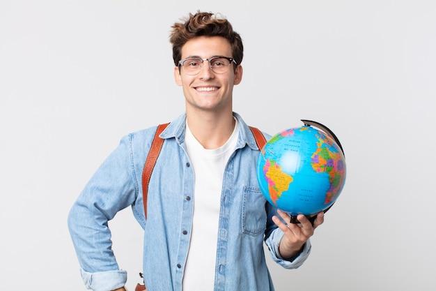 Jonge knappe man glimlachend gelukkig met een hand op de heup en zelfverzekerd. student met een wereldbolkaart