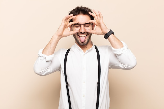 Jonge knappe man glimlachend gelukkig met grappig gezicht, grappen maken en kijken door kijkgaatje, geheimen bespioneren