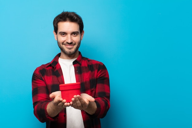 Jonge knappe man glimlachend gelukkig met vriendelijke, zelfverzekerde, positieve blik, een object aanbieden