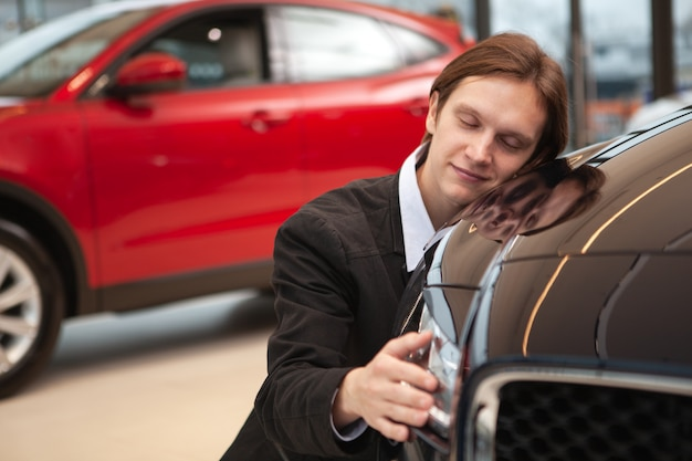 Jonge knappe man glimlachend met zijn ogen dicht, nieuwe auto omarmen bij de dealer