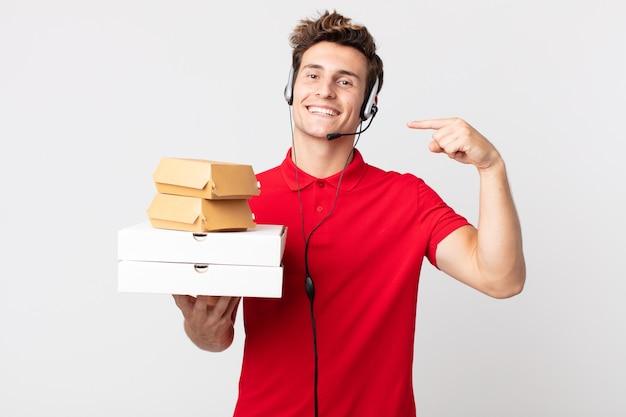 Jonge knappe man glimlachend vol vertrouwen wijzend naar eigen brede glimlach. afhaal fastfood concept