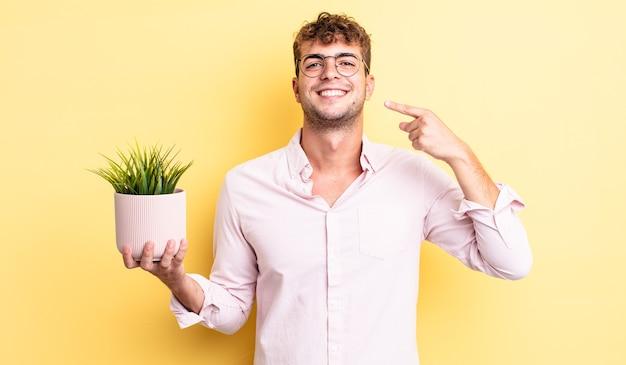 Jonge knappe man glimlachend vol vertrouwen wijzend naar eigen brede glimlach. decoratief plantenconcept