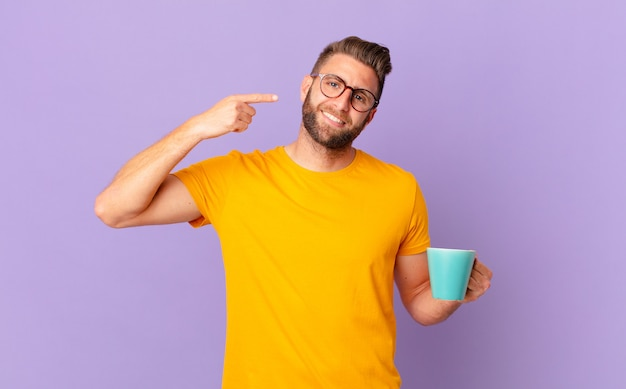 Jonge knappe man glimlachend vol vertrouwen wijzend naar eigen brede glimlach. en een koffiemok vasthouden