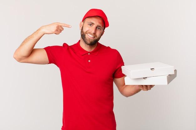 Jonge knappe man glimlachend vol vertrouwen wijzend naar eigen brede glimlach. pizza bezorgconcept