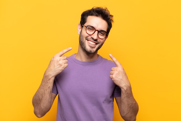 Jonge knappe man glimlachend vol vertrouwen wijzend naar eigen brede glimlach, positieve, ontspannen, tevreden houding