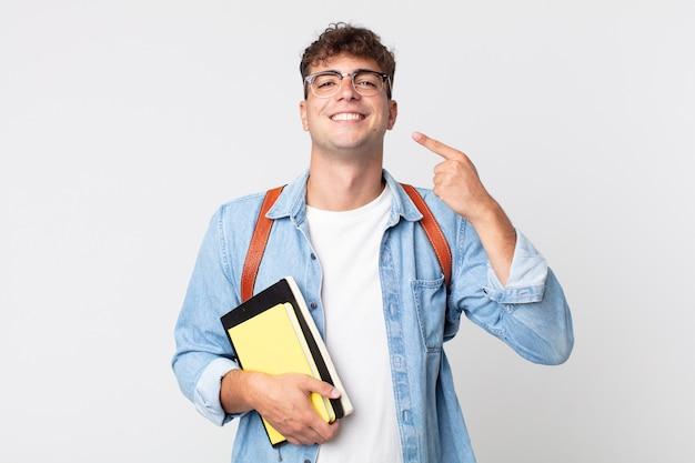 Jonge knappe man glimlachend vol vertrouwen wijzend naar eigen brede glimlach. universitair studentenconcept