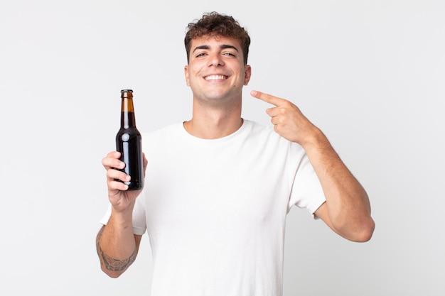 Jonge knappe man glimlachend vol vertrouwen wijzend naar zijn eigen brede glimlach en een bierflesje vasthoudend