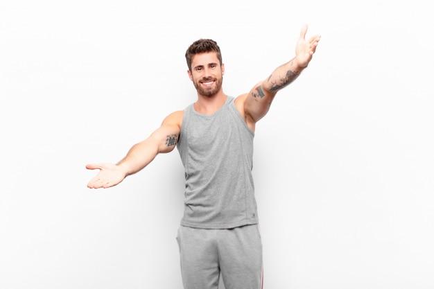 Jonge knappe man glimlachend vrolijk geven een warme, vriendelijke, liefdevolle welkomstomhelzing, zich gelukkig en schattig voelen. sport concept