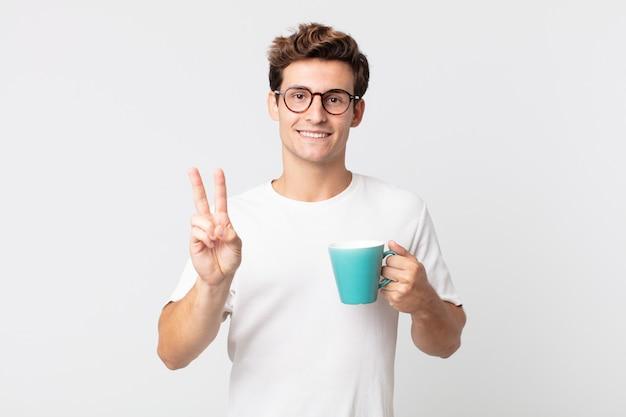 Jonge knappe man glimlacht en ziet er gelukkig uit, gebaart overwinning of vrede en houdt een koffiekopje vast