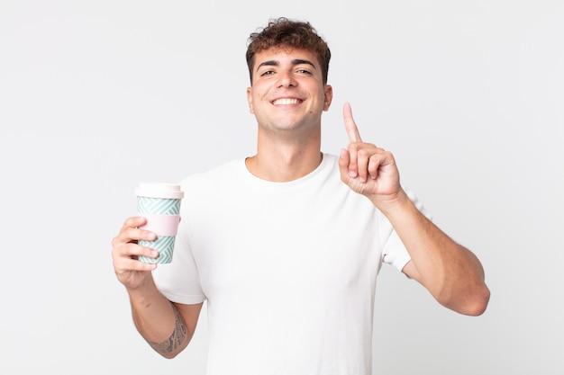 Jonge knappe man glimlacht en ziet er vriendelijk uit, toont nummer één en houdt een afhaalkoffie vast