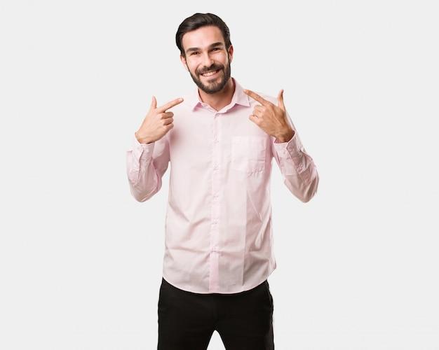 Jonge knappe man glimlacht, wijzend op mond