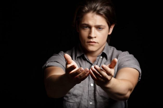 Jonge knappe man handen uitrekken aan camera