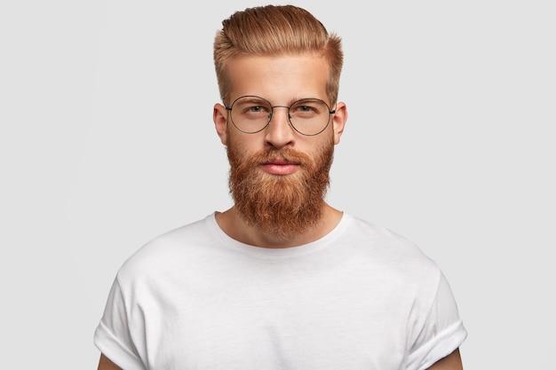 Jonge knappe man hipster heeft dikke gemberbaard en snor, trendy kapsel, kijkt je serieus rechtstreeks aan