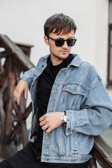 Jonge knappe man hipster in een modieuze blauwe denim jasje in stijlvolle zonnebril in zwarte spijkerbroek rust in de stad in de buurt van vintage gebouw. aantrekkelijke man ontspant buiten in de stad. herenkleding.