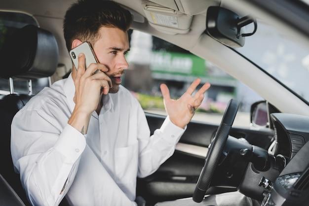 Jonge knappe man in auto praten op mobiele telefoon gebaren