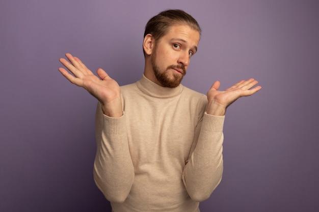 Jonge knappe man in beige coltrui die naar de voorkant kijkt, verward en geen idee met open armen die over lila muur staan