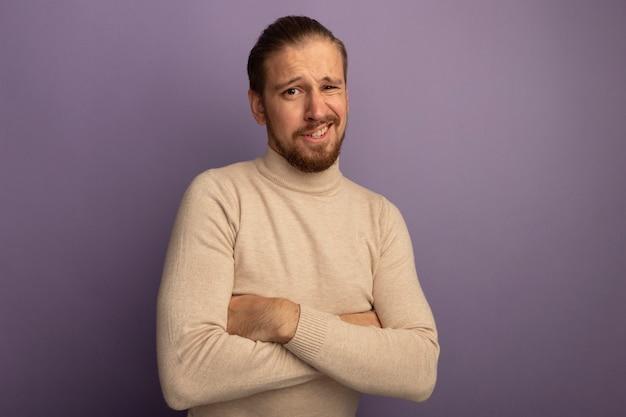 Jonge knappe man in beige coltrui die naar de voorkant kijkt, verward met gekruiste armen op zijn borst die over lila muur staat