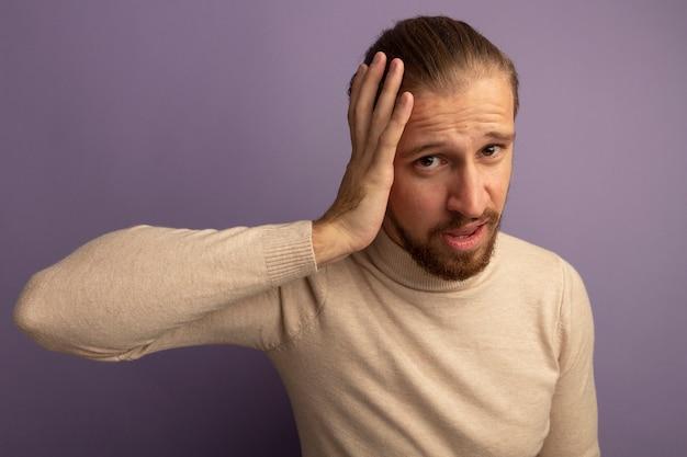 Jonge knappe man in beige coltrui die naar voorkant kijkt, verward met de hand op zijn hoofd voor een fout die over de lila muur staat