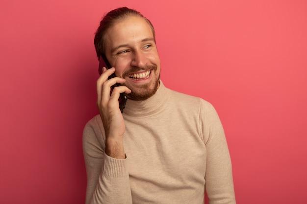 Jonge knappe man in beige coltrui die vrolijk glimlacht terwijl hij op mobiele telefoon praat die zich over roze muur bevindt