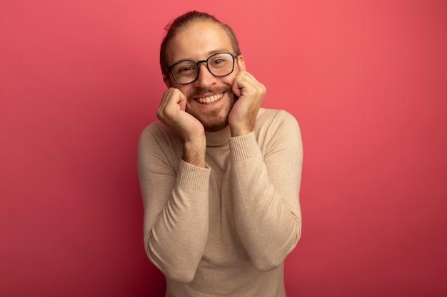 Jonge knappe man in beige coltrui en bril kijken naar voorkant glimlachend vrolijk gevoel positieve emoties staande over roze muur