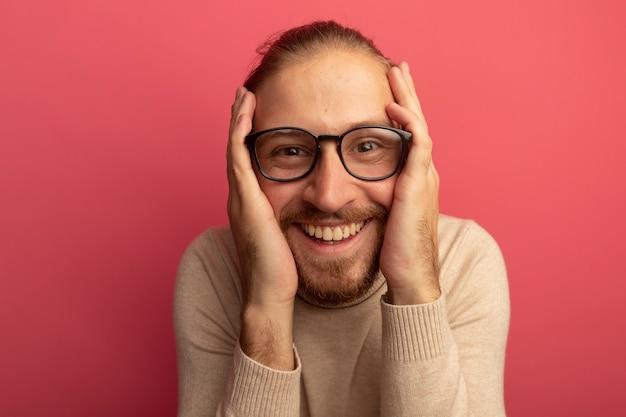 Jonge knappe man in beige coltrui en glazen kijken voorkant verbaasd en verrast staande over roze muur