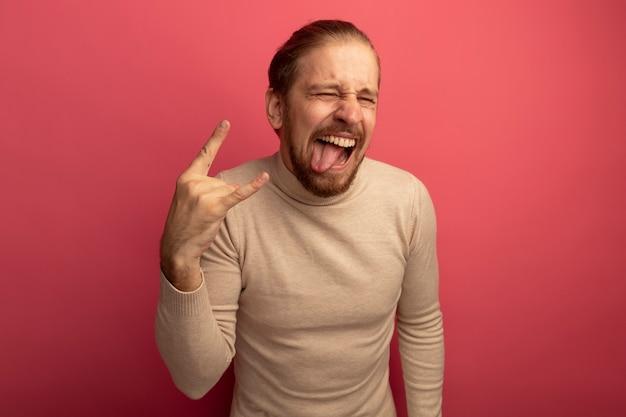 Jonge knappe man in beige coltrui gek gelukkig tong uitsteken waardoor rock symbool staande over roze muur