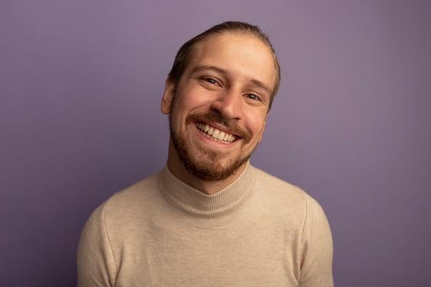 Jonge knappe man in beige coltrui glimlachend in grote lijnen met tanden