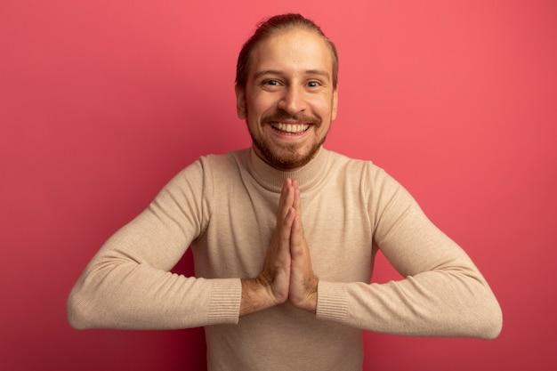 Jonge knappe man in beige coltrui hand in hand als namaste gebaar blij en vrolijk staande over roze muur