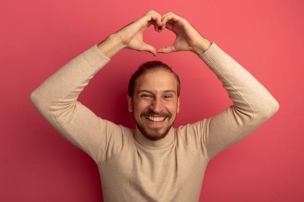 Jonge knappe man in beige coltrui hart gebaar met vingers boven zijn hoofd glimlachend vrolijk maken