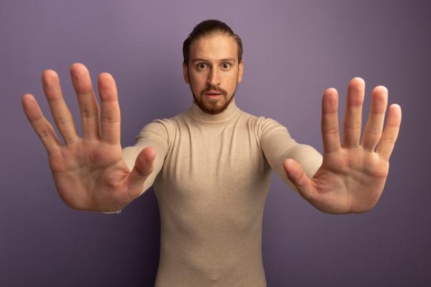 Jonge knappe man in beige coltrui kijken naar voorkant bezorgd stop gebaar maken met open handen staande over lila muur