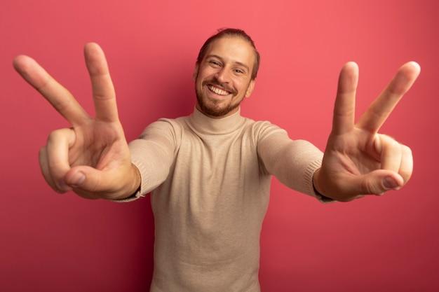Jonge knappe man in beige coltrui kijken naar voorkant glimlachend vrolijk tonen v-teken met beide handen staande over roze muur