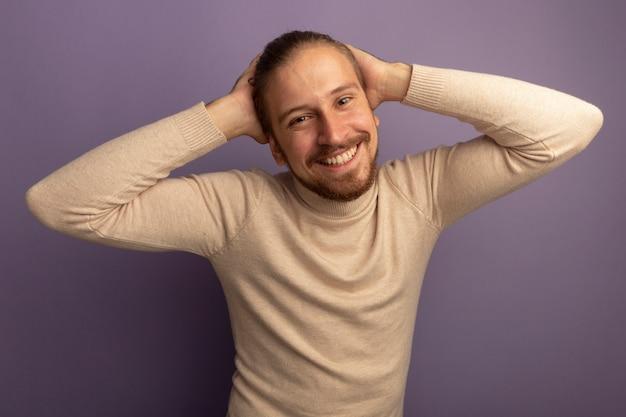 Jonge knappe man in beige coltrui kijken naar voorkant lachend met blij gezicht met handen op zijn hoofd staande over lila muur