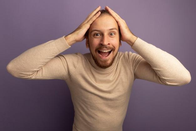 Jonge knappe man in beige coltrui lachend met blij gezicht met handen op zijn hoofd
