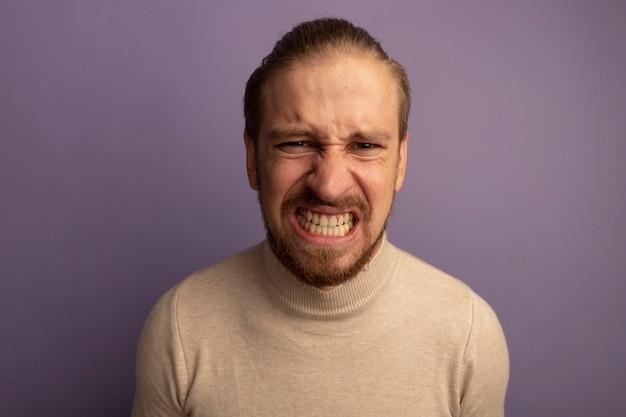 Jonge knappe man in beige coltrui met boos gezicht geïrriteerd