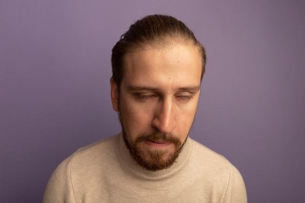 Jonge knappe man in beige coltrui met droevige uitdrukking