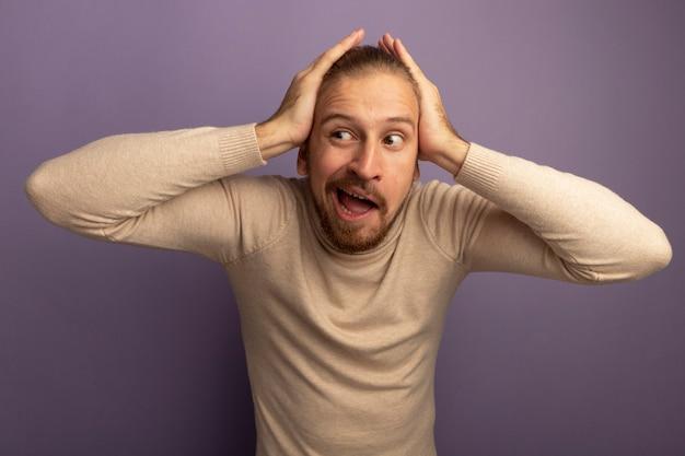 Jonge knappe man in beige coltrui opzij kijken met handen op zijn hoofd lachend