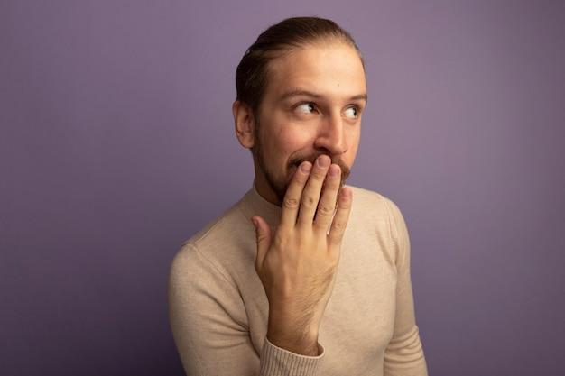 Jonge knappe man in beige coltrui opzij kijken verrast bedekkende mond met hand