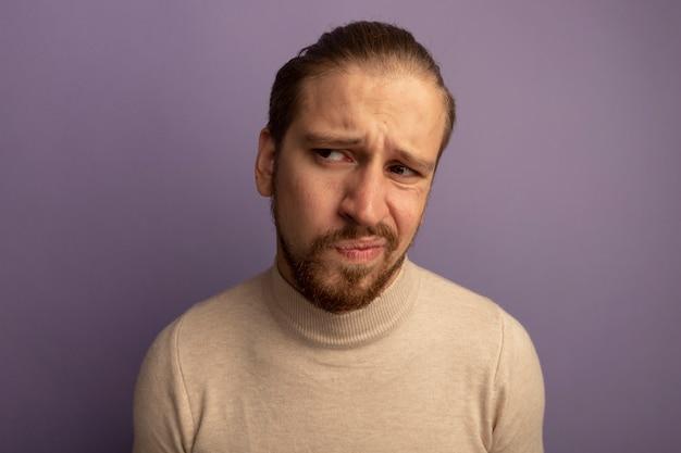 Jonge knappe man in beige coltrui opzij kijken verward en ontevreden
