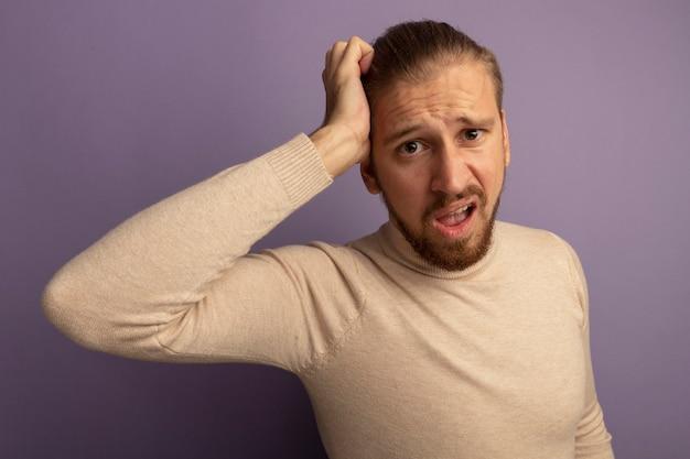 Jonge knappe man in beige coltrui verward met de hand op zijn hoofd