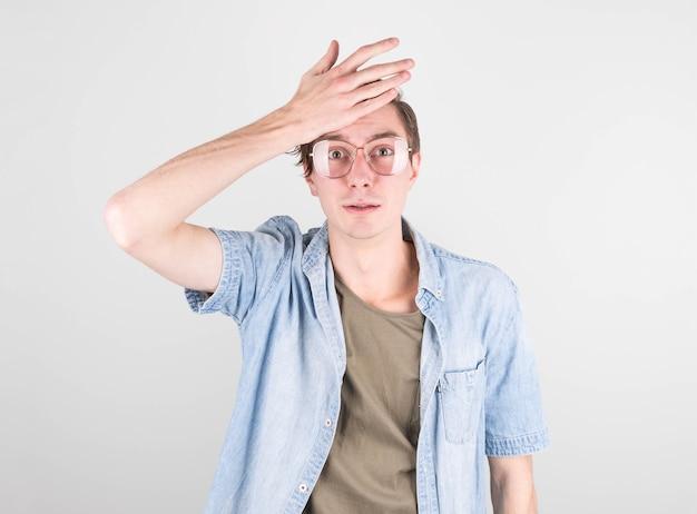 Jonge knappe man in casual t-shirt, staande tegen een witte muur, beschaamd en verwonderd. onzeker van twijfel, nadenkend, zijn hand op zijn hoofd leggen. doordacht concept.