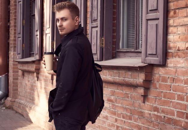 Jonge knappe man in donkere jas met kopje koffie
