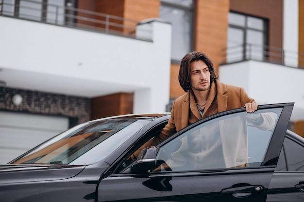 Jonge knappe man in een auto zit