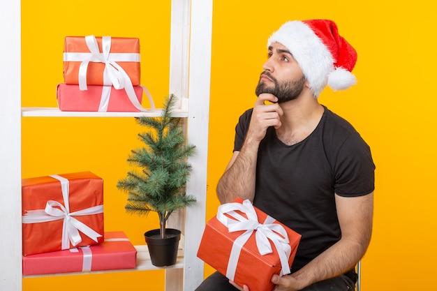 Jonge knappe man in een kerstman hoed houdt felicitaties naast een kerstboom. concept vakantie van kerstmis en nieuwjaar.