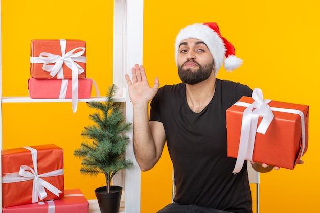 Jonge knappe man in een kerstman hoed houdt felicitaties naast een kerstboom