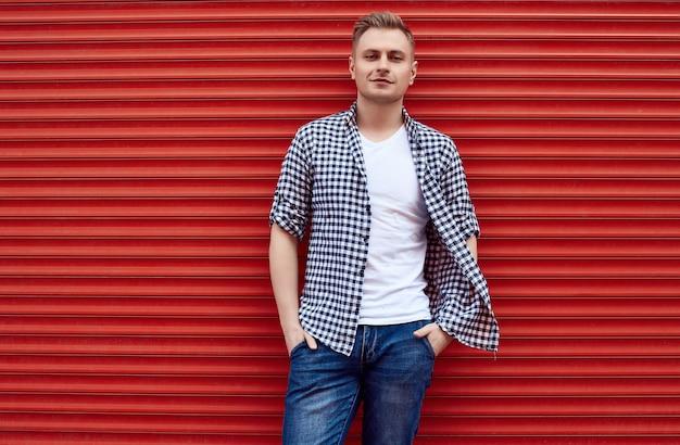 Jonge knappe man in een shirt en spijkerbroek in de buurt van de rode poort